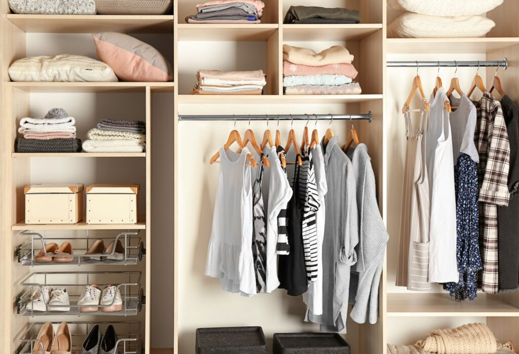 Large wardrobe closet with different clothes and shoes